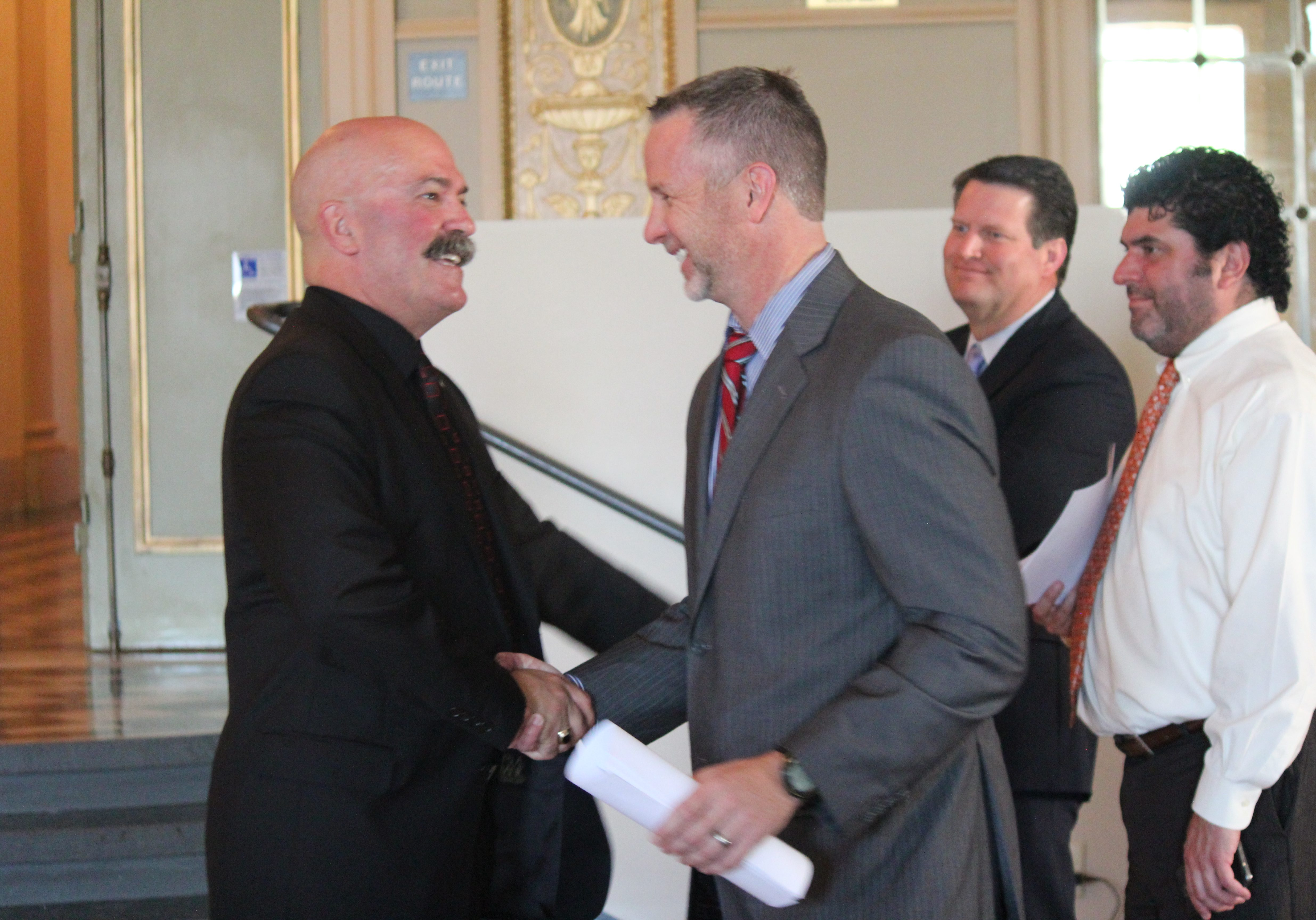 Two male members of the california trucking association shake hands.